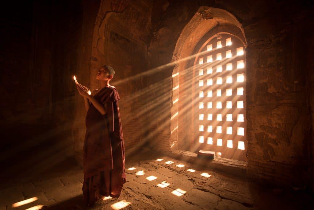 Buddhist monk praying in light rays