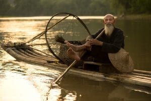 A cormorant fisherman in Guilin China takes five on his raft