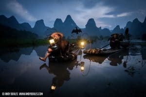 Guilin's cormorant fishermen reflecting on the calm Li River with their kerosine lamps in the dusk light.
